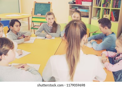 Elementary age group of pupil with young teacher sitting at table and studying