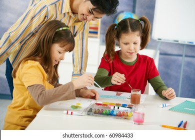 Elementary age pupils sitting around desk enjoying painting with colors in art class at primary school classroom.?