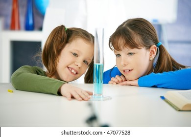 Elementary age school girls looking at test tube in chemistry class at primary school.