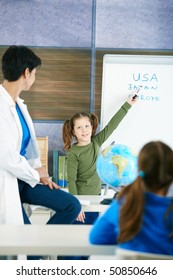 Elementary age schoolgirl at whiteboard answering to teacher in geography lesson.