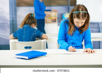 Elementary age schoolgirls writing tests at class seated aside, teacher standing in the background.