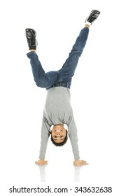 An elementary boy delightedly standing on his hands.  On a white background.