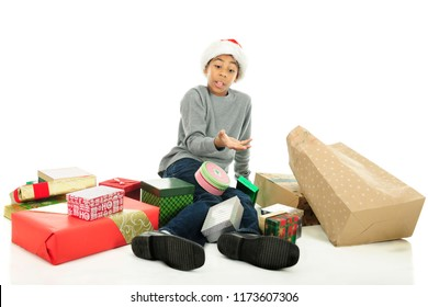 An elementary boy fallen on the floor surrounded by the Christmas gifts he dropped.  On a white background.
