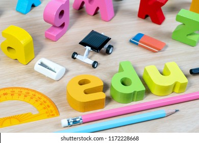 Elementary classroom table with wooden word EDU and education supplies for school background. School objects for Education.