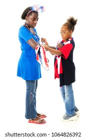 An elementary gilr helping her tween sister tie a scarf around her big sister's arm as a display of their American patriotism.  On a white background.