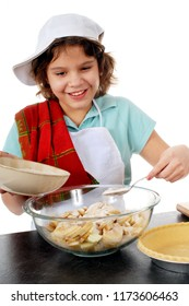 An elementary girl happily adding sugar to the apple slices she's preparing for the nearby pie shell.  On a white background.