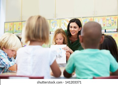 Elementary Pupil Showing Drawing To Classmates In Classroom