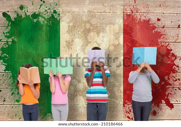 Elementary pupils reading against italy flag in grunge effect
