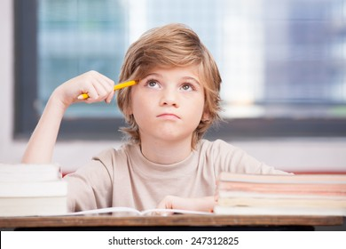Elementary school boy at classroom desk trying to find new ideas for schoolwork.