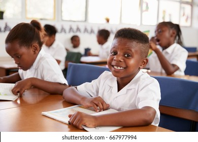 Elementary school boy smiling at camera at his desk in class
