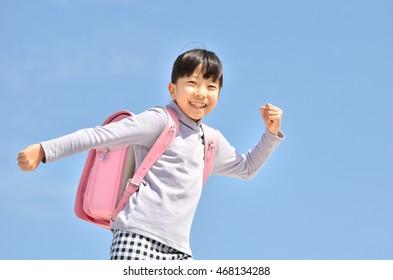 Elementary school children running in the blue sky