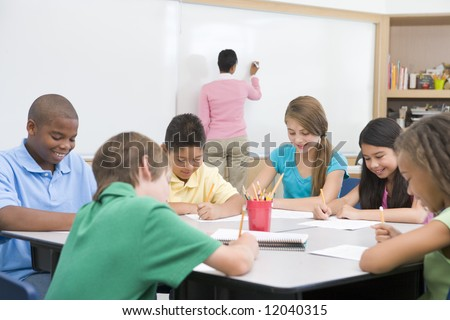 Elementary school clasroom with teacher writing on board