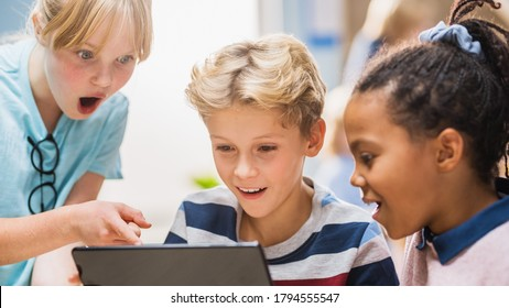 Elementary School Computer Science Class: Two Girls and Boy Use Digital Tablet Computer with Augmented Reality Software, They're Excited, Full of Wonder, Curiosity. Children in STEM, Playing, Learning