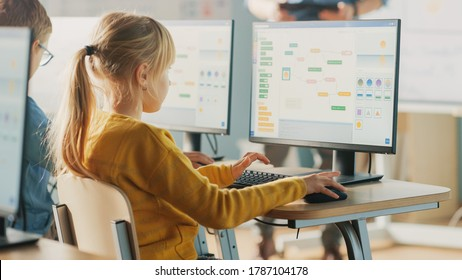 Elementary School Computer Science Classroom: Cute Little Girl Uses Personal Computer, Learning Programming Language for Software Coding. Schoolchildren Getting Modern Education. Over the Shoulder