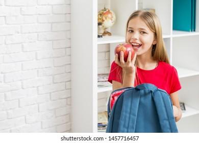Elementary school girl intending to bite apple