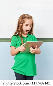 Elementary school girl looks in astonishment at her tablet computer