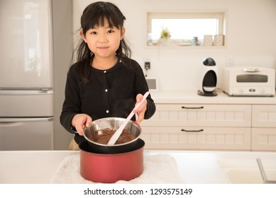 Elementary school girl making homemade chocolate