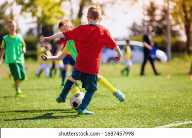 Elementary school kids playing football in a field. Boys kicking soccer on the sports grass pitch. Children in sportswear on football match