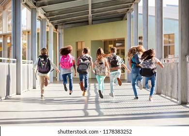 Niños de la escuela primaria corriendo en la escuela, vista posterior cerrada