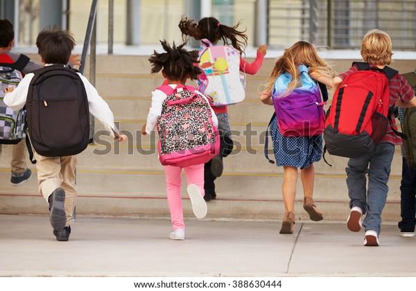 Enfants de l'école primaire courant à l'école, vue arrière