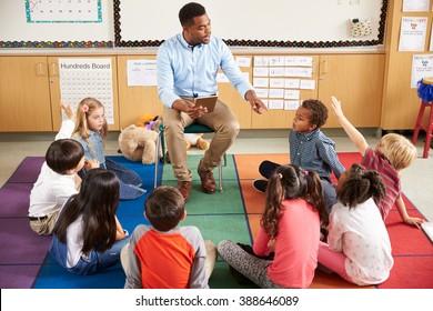 Elementary school kids sitting around teacher in a lesson
