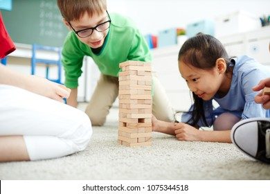 Elementary school kids sitting on the floor and playing with wooden block stack  after classes at school