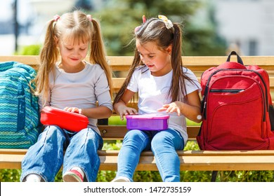 Elementary school kids sitting with packed lunches