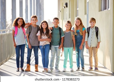 Elementary school kids stand in corridor looking at camera