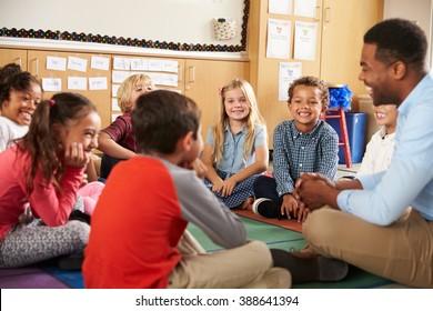Elementary school kids and teacher sit cross legged on floor