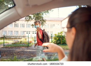 Elementary school learner going to school in the morning wearing protective mask. His mother on the foreground waving from the car.  Concept of school education during the Covid-19 pandemic