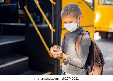 Elementary school learner sanitizing hands before going into the school bus in the morning. Concept of personal hygiene and education during the pandemic