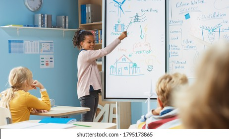 Elementary School Science Class: Cute Girl Uses Interactive Digital Whiteboard to Show to a Classroom full of Classmates how Renewable Energy Works. Science Class, Curious Kids Listening.