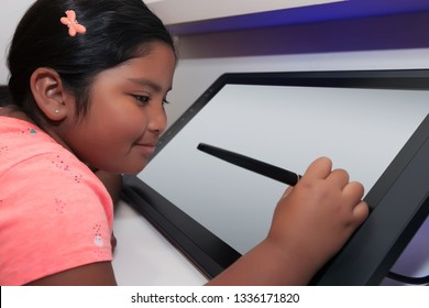 Elementary school student holding a pen like stylus and drawing on a digital drawing tablet.