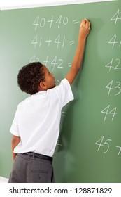 elementary school student writing maths answer on chalkboard