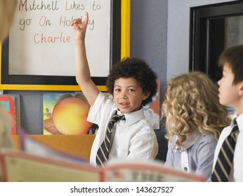 Elementary schoolboy giving answer in class with hand raised