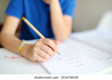 Elementary student boy doing homework at home. Child learning to count, solves arithmetic examples, doing exercises in workbook. Math tutorial. Preparing preschooler baby for school.Education for kids