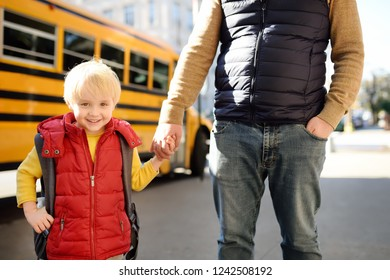 Elementary student hold hands his father near yellow school bus on background. Back to school.