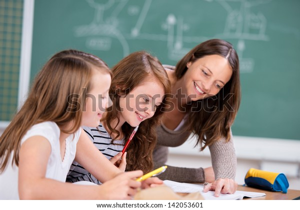 Elementary students listening to female teacher in school classroom