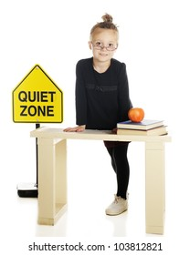 "An elementary-aged ""teacher"" standing behind her desk by a ""Quiet Zone"" sign.  On a white background."
