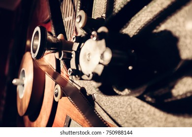 Elements of an old cinematic machinery. Reels with film tape. Vintage movie industry. Close-up picture.