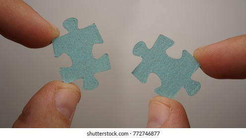 Elements of the puzzle going into a whole. As a symbol of various business solutions. Man and woman joining puzzle jigsaw concept isolated on white or gray background