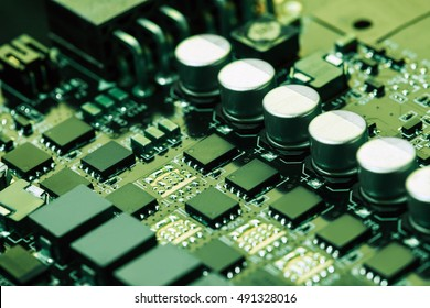 Elements of the video card power supply circuit: capacitors, thyristor, resistor and other. Low aperture shot, selective focus. Green tone image.