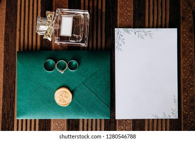 Elements of wedding decor. Wedding rings, perfume, green envelope postcard and invitation. Top view, flat lay