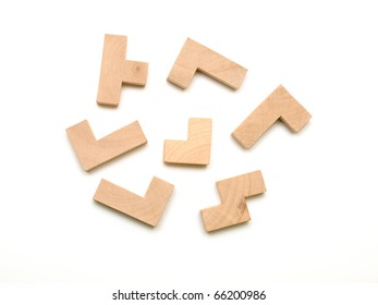 Elements of a wooden puzzle randomly placed on white background