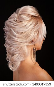 Elengance hair style of young beautiful woman with blonde hair in studio. Stylish coiffure. Modern style.