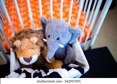 Elepant and lion stuff animals in basket next to soft-focused background of newborn orange bed
