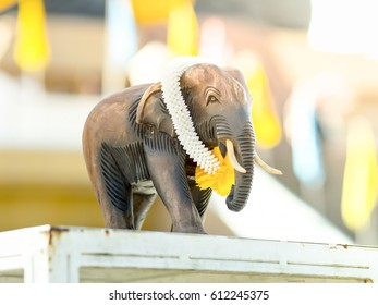 Elephant figurine hand wood carved with fake jasmine and marigold garland.