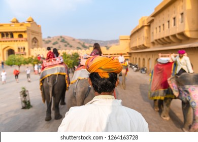 Elephant rider (mahout) in traditional rajasthani turban rides an elephant in Amber Fort, India