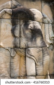 Elephants stone sculpture on the wall in public garden, Thailand