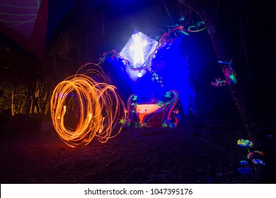 Eletronic music festival decoration, fire juggling in long exposure. Night in the forest. Florianópolis, Santa Catarina / Brazil
